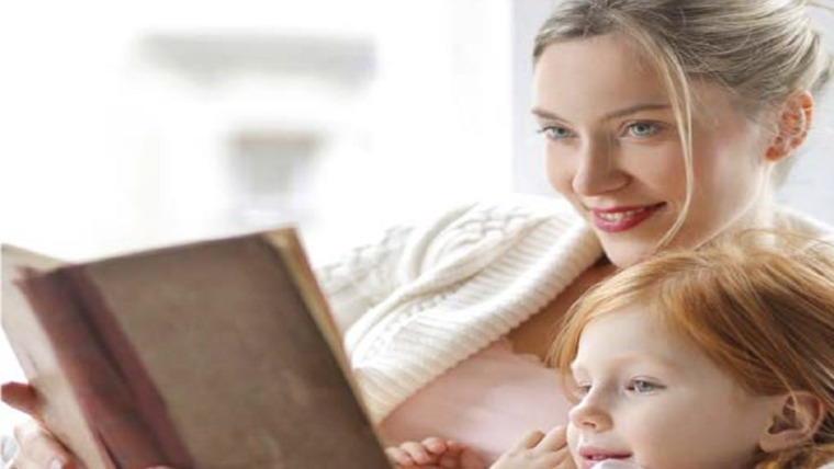 mother reading story to daughter in bed