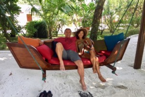 husband & wife lounging on a long wooden swing seat