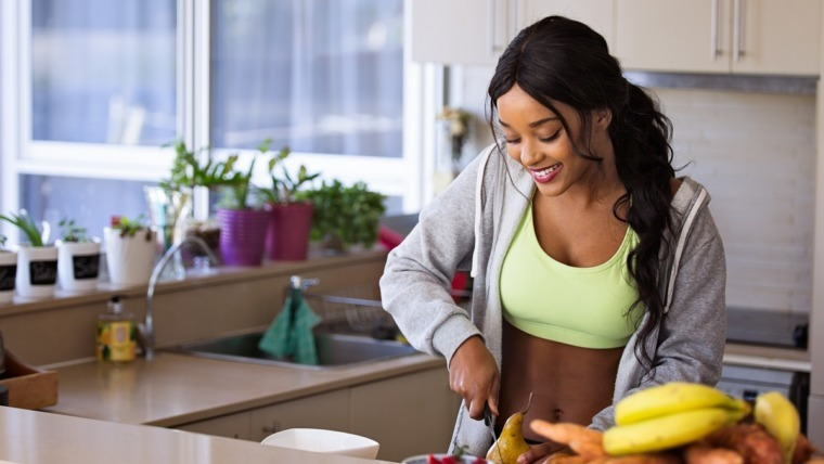 young woman in running gear at kitchen slicing pear