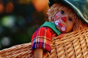 child doll in basket wearing gingham shirt
