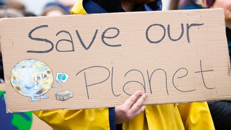 protester holding cardboard sign saying save our planet