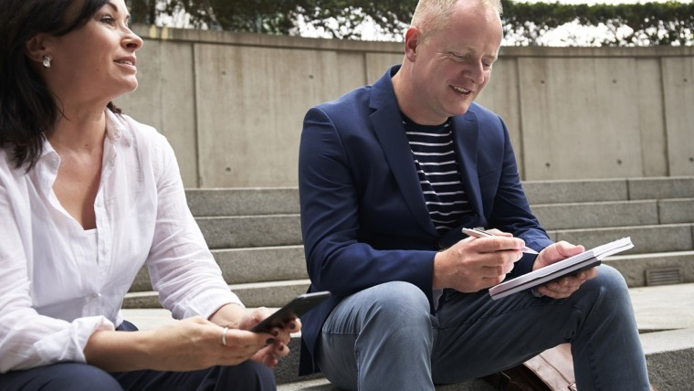 woman with phone and man with note pad and pen sitting outside