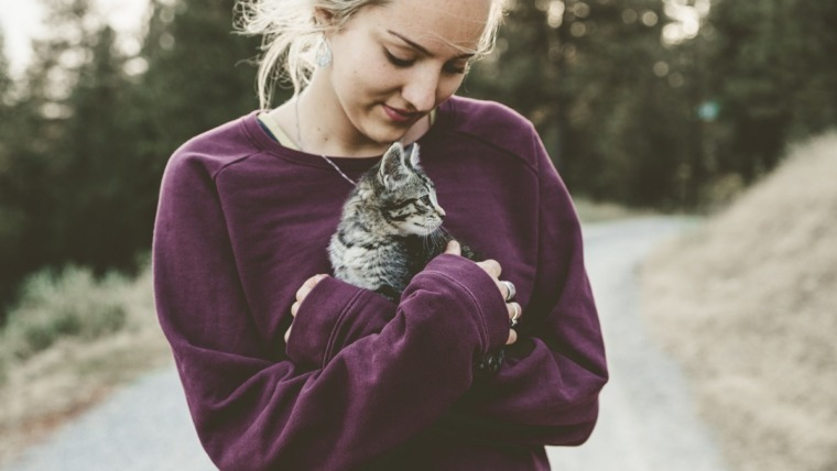 woman holding cat in purple pullover