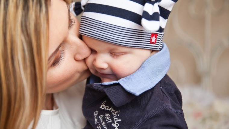 mother kissing baby in stripped cap