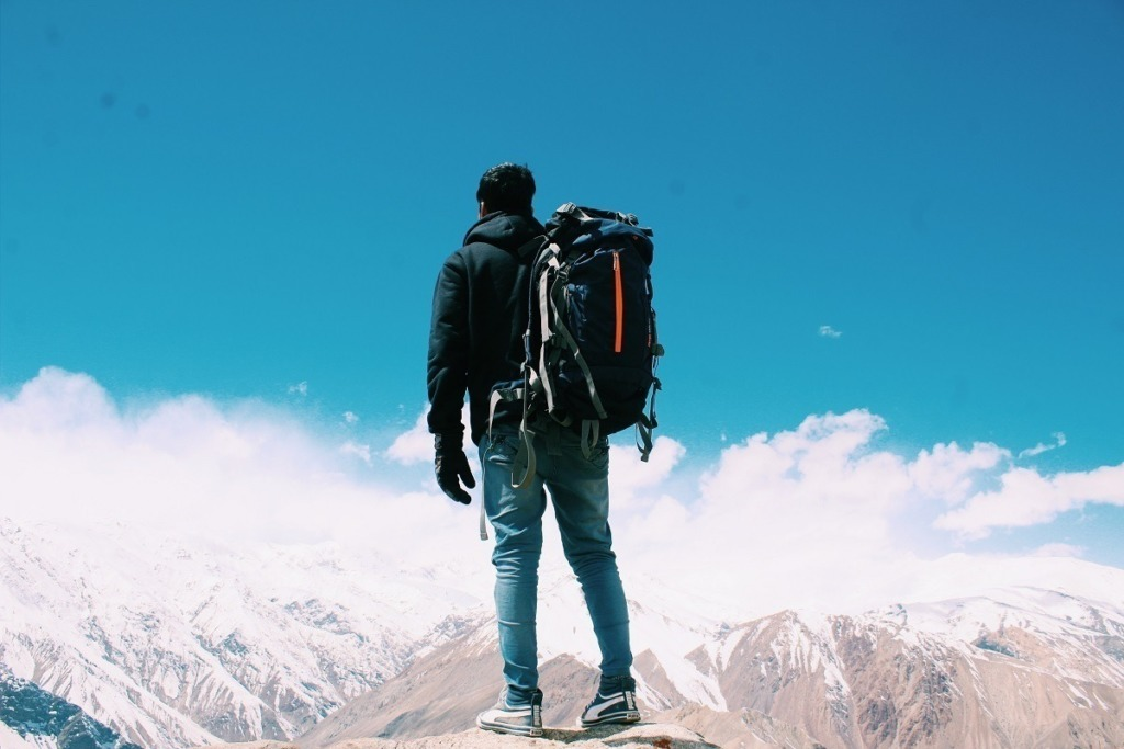 man with backpack looking at snow topped mountains